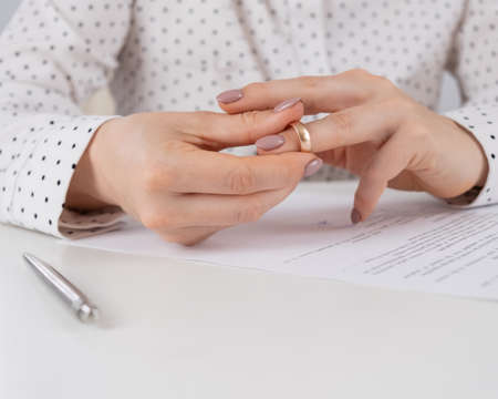 Close-up woman signed divorce papers and took off her wedding ring