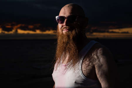 A humorous portrait of a brutal man in a T-shirt and boxers on the beach at sunset Stockfoto