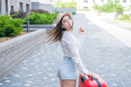 Young caucasian woman in a hat and shorts stands on the street with a red suitcase. Stockfoto