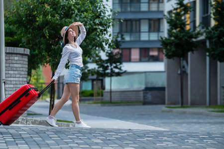 Happy caucasian young woman in a hat and shorts is holding a big red suitcase is walking on a city street Stockfoto