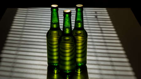 Three green glass beer bottles in the shade of the blinds. Stockfoto
