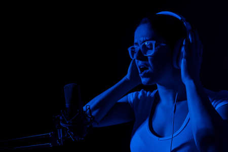 Caucasian woman in glasses and headphones sings into a microphone in neon light on a black background. An emotional girl is recording a song in a recording studio
