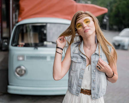 Pensive hippie girl at the classic blue van