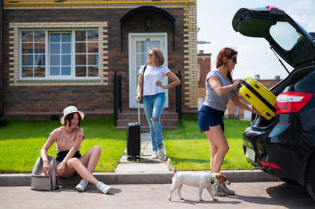 Three Caucasian women and a dog are going on a road trip. The girls are loading their suitcases into the trunk of the car. Summer vacation concept together with girlfriends.