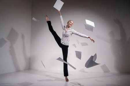 A graceful ballerina in a business suit throws documents in the studio. Business woman dance barefoot on a white background Stockfoto