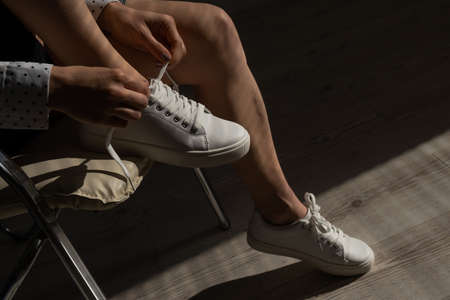 Woman put on new white leather sneakers Stockfoto