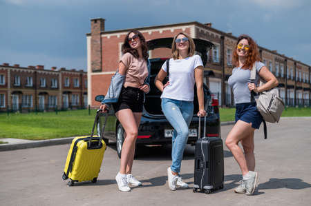 Three friends are going to travel by car. Summer vacation Stockfoto