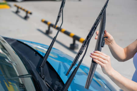 Faceless woman changing car windshield wipers.