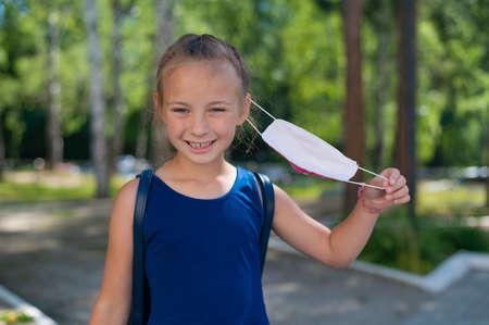 Happy schoolgirl took off her protective mask.