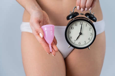 Close-up of a woman in white cotton panties holding a pink menstrual cup and an alarm clock on a white background. Alternative to tampons and pads