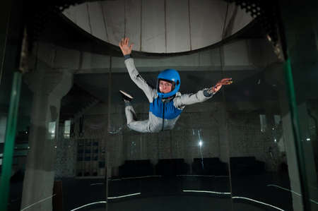 A young woman in overalls and a protective helmet enjoys flying in a wind tunnel. Free fall simulator