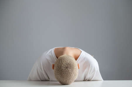 Sad woman sitting with her head on the table on a white background. 写真素材