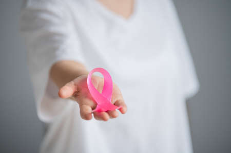 A faceless woman wearing a white t-shirt holds a pink ribbon as a symbol of breast cancer on a white background.