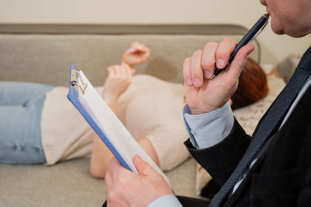 Caucasian woman lies on a couch at a reception with a psychotherapist. An elderly man works as a psychiatrist