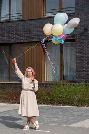 Woman in colored hair walks with an armful of balloons and drinks a refreshing beverage 写真素材