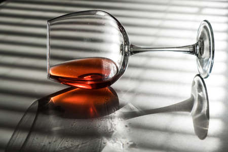 A glass of red wine lies on its side on a white table with a shade from the blinds