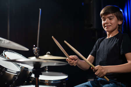 A boy plays drums in a recording studio