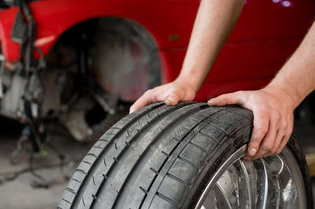 An auto mechanic holds a wheel of a car. Change of car tires according to the season