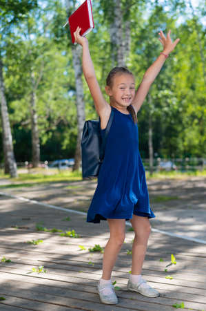 Joyful schoolgirl jumping outdoors. End of summer vacation and start of the primary school year 写真素材