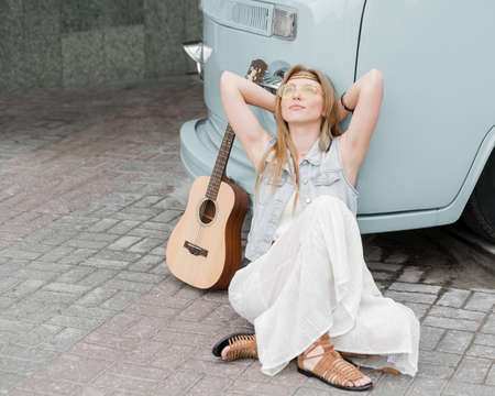 A hippie woman sits on the sidewalk and plays guitar next to a classic minivan.