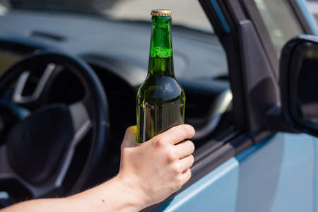 A faceless woman is drinking a bottle of beer while driving a car. Breaking the law and drinking alcohol while driving 写真素材