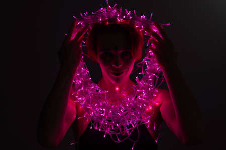Woman with witch makeup and an earring in her nose. The girl holds a garland of flickering pink lights near her face. Light bulbs illuminate the witchs face in the dark. 写真素材
