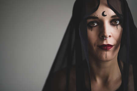 Redhead woman with a black veil on her head in a dark studio. A girl with an earring in her nose smiles slyly. Witch Makeup. Halloween costume. 写真素材