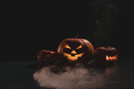 Pumpkins with carved grimaces and candles inside in the dark for halloween. Jack o latern in smoke. 写真素材