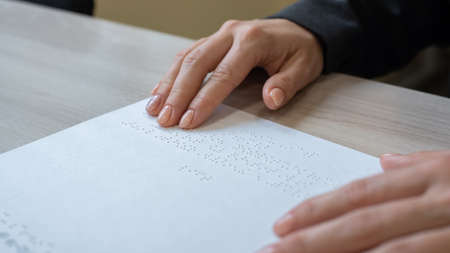 Close-up woman reads the text to the blind. Womans hands on paper with braille code.