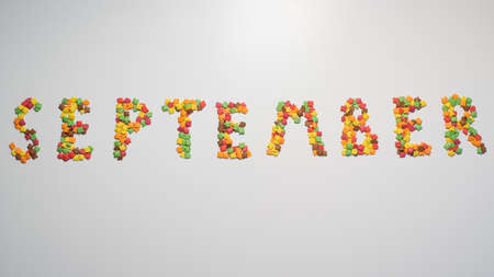 The inscription September on a white background. Confectionery sprinkles in the form of multi-colored maple leaves. Widescreen.