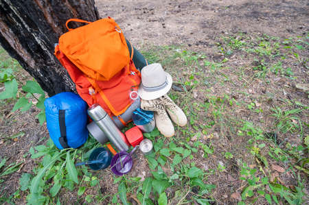 Hiking equipment in a pine forest. Backpack, sleeping bag, compass, hat and shoes