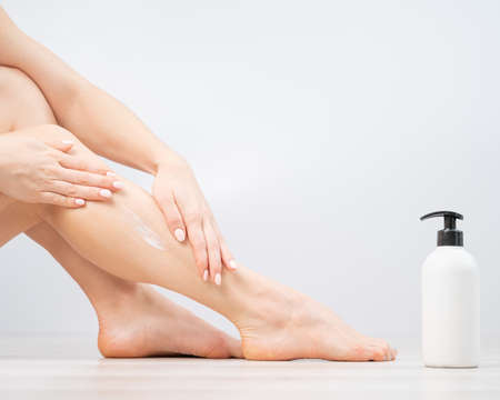 Woman applies moisturizer to her legs on a white background. The girl takes care of the skin and uses the cream.