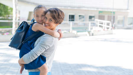 Woman holding schoolgirl daughter in her arms outdoors