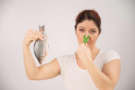 Caucasian woman with a clothespin on her nose because of the disgusting smell of fish. A metaphor for womens health and intimate hygiene. 写真素材