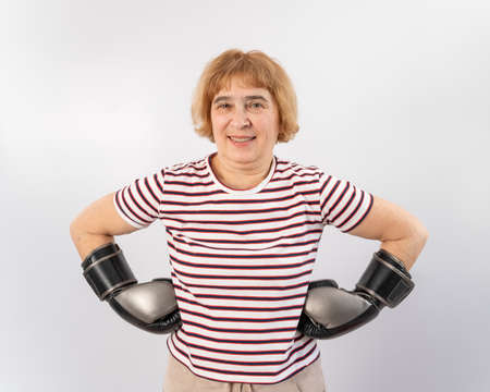 Elderly woman in fighting gloves in a defensive pose on a white background.