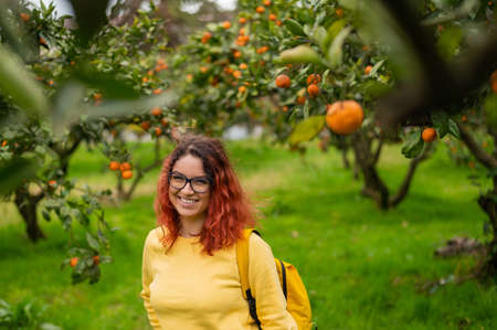 Red-haired smiling woman stands in the tangerine garden. 写真素材