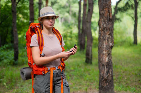 Young caucasian woman is hiking and using a compass in the forest. 写真素材