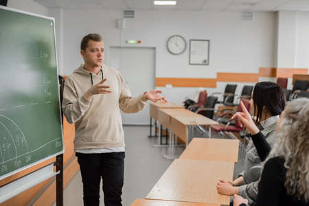 Two girls and a guy are talking in sign language. Three deaf students chatting in a university classroom.