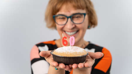 A portrait of a smiling elderly woman in a festive cap holding a cake with candles in the form of the number 60. Anniversary