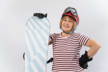 Portrait of smiling elderly woman in pink ski helmet gloves and with snowboard on white background.