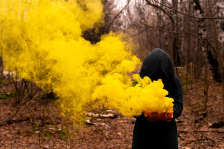A creepy witch holds a steaming pumpkin in a deep forest. Jack o lantern emits yellow smoke for halloween