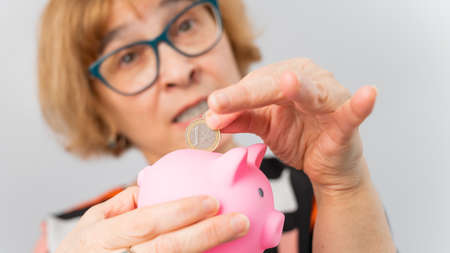 An elderly woman with glasses puts a coin in a piggy bank on a white background