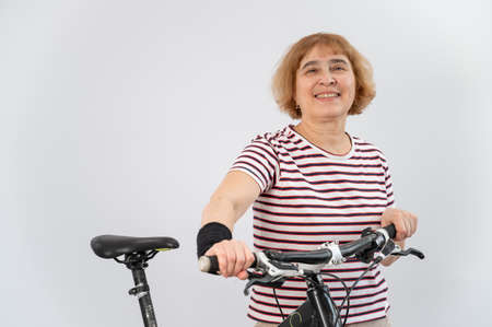 Elderly woman on a bicycle on a white background.
