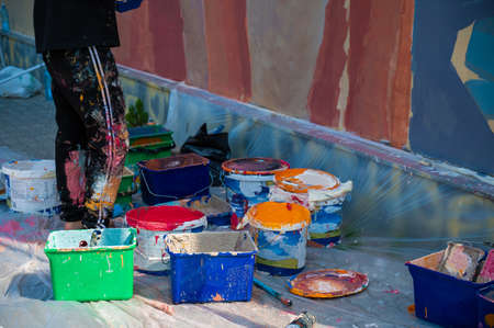A street artist paints on the wall. close-up of paint buckets.