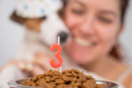 Caucasian woman congratulates her dog on the 3rd birthday. Jack Russell Terrier blows out the candle