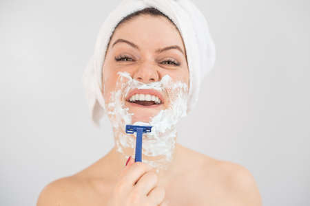 A woman with a white terry towel on her head and with shaving foam on her face shaves on a white background