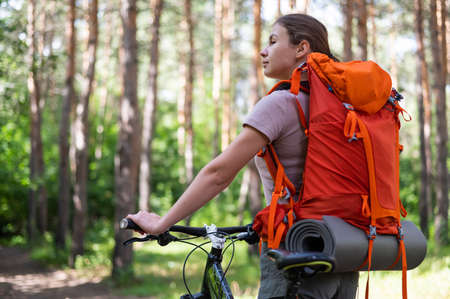 Caucasian woman rides a bicycle in the forest 写真素材