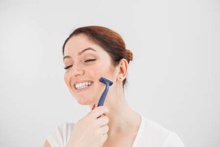 Caucasian funny woman shaves her face with a straight razor on a white background. Copy space.