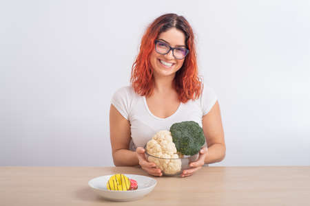 Caucasian woman prefers healthy food. Redhead girl chooses between broccoli and donuts on white background.