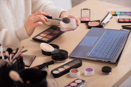 A faceless woman watches online training from a professional makeup artist on a laptop. Distance learning 写真素材